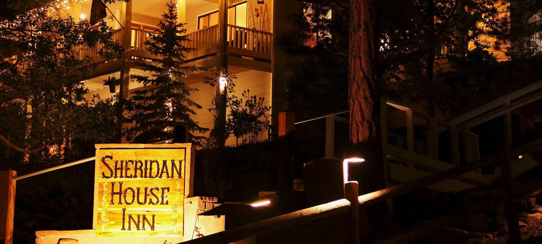 Nighttime outside of a two story home in the woods with glowing porch lights and inn sign lit up