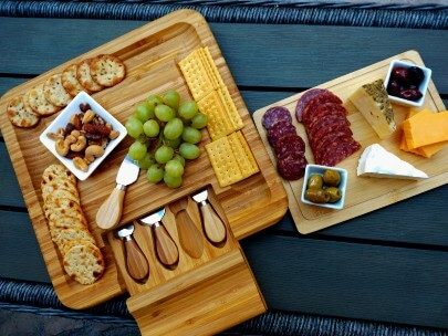 Two wooden charcuterie boards with fruit, crackers, cheese, meat and nuts on a black table