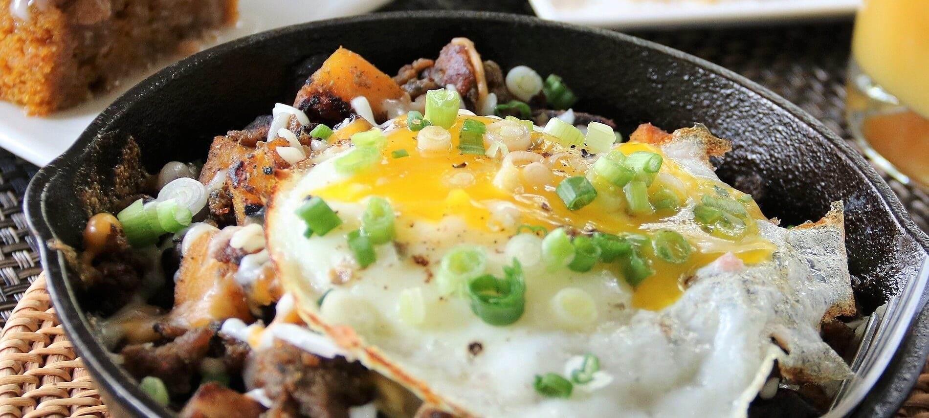 Cast iron pan filled with breakfast hash of meat and potatoes topped with fried eggs and diced green onion