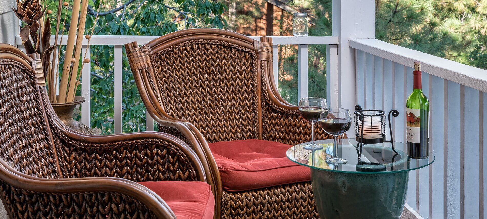 Two brown wicker chairs with red cushions on a porch with white railing and glass side table holding bottle of wine and two glasses half full