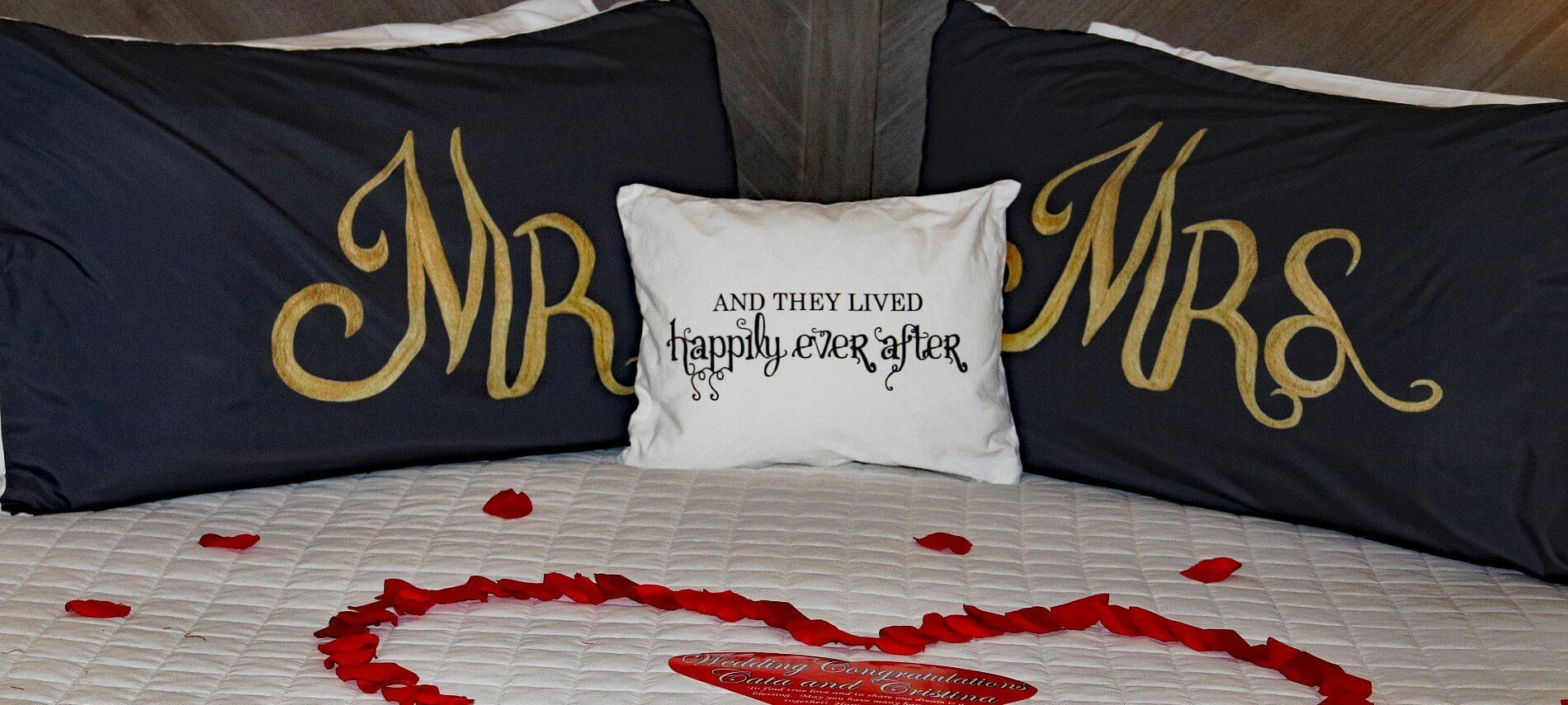 Bed with Mr and Mrs pillows and red flower petals in the shape of a heart