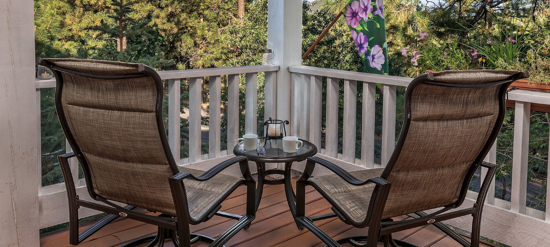 Two metal framed patio chairs with side table holding coffee cups outside viewing a wooded area