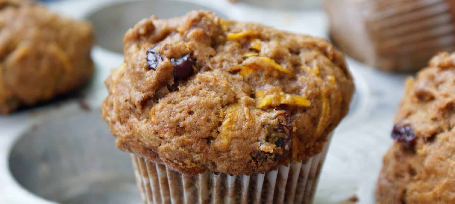 Delicious carrot and fruit muffin with a white wrapper on a white plate