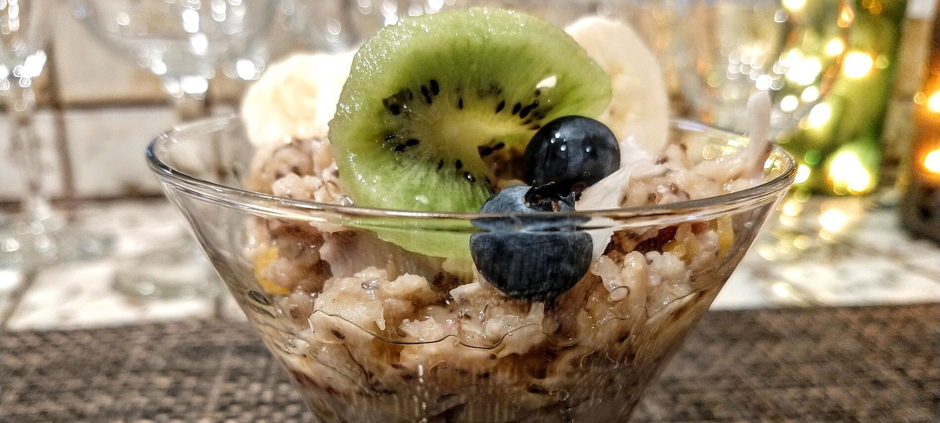 Glass bowl with homemade oatmeal and slice of kiwi, blueberries and sliced bananas