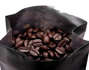 Open bag of dark brown coffee beans against a white background