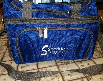 Blue cooler with grey straps and zippered pockets sitting on a tiled countertop
