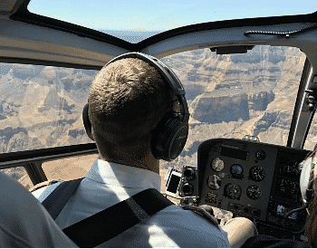 Man in white shirt and headphones piloting a helicopter with views of rock and canyon through the windows