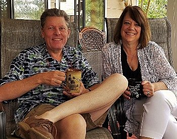 Woman with brown hair in white pants and shirt sits next to a man in shorts and dress shirt, each holding cups of coffee