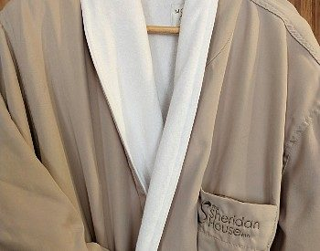 Front of a luxurious beige and white robe with an inn logo hanging on a hanger