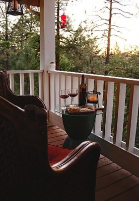 Two brown chairs with a glass-topped side table holding a wine bottle, glasses and plate of snacks on a small outdoor patio
