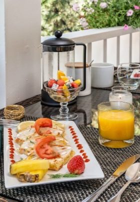 Glass top wicker table outside on a patio with breakfast plate, orange juice, coffee and dish of fresh fruit