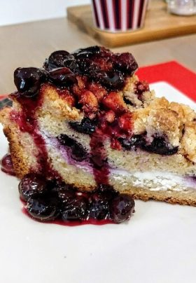 One slice of blueberry crumble pie with blueberry compote topping on a white plate