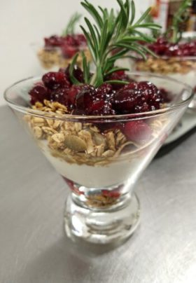 glass dish with yogurt, granola and cranberry sauce with rosemary sprig on top