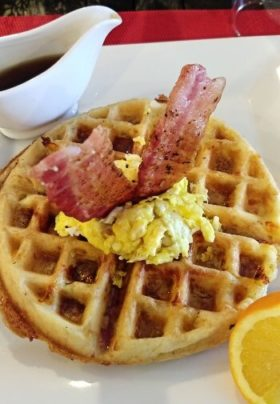 waffle with scrambled eggs and bacon on top with syrup on side