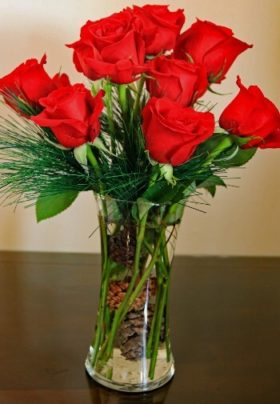 red roses in a clear vase with pine cones and pine boughs
