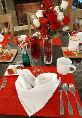 Breakfast table set for Valentine's Day with red placemats, vase of red roses and napkins folded into hearts