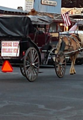 Horsedrawn carriage rolling down street