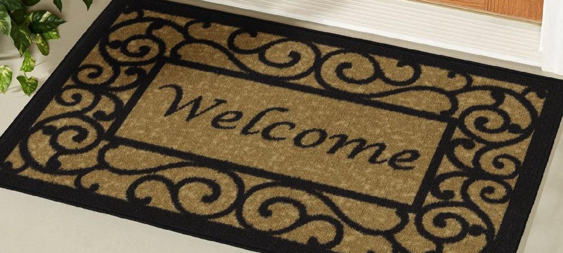 Large brown and black welcome mat with scroll design on the floor in front of a door